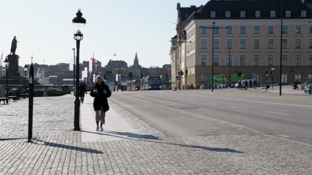 exterior shots of commuters walking, on bikes etc with buses and cars passing along historic city centre stree past stockholms ström on 3 april 2020... - svezia video stock e b–roll