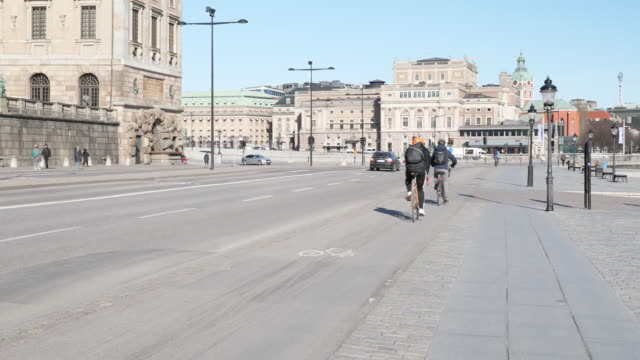 exterior shots of commuters walking, on bikes etc with buses and cars passing along historic city centre stree past stockholms ström on 3 april 2020... - stockholm stock videos & royalty-free footage