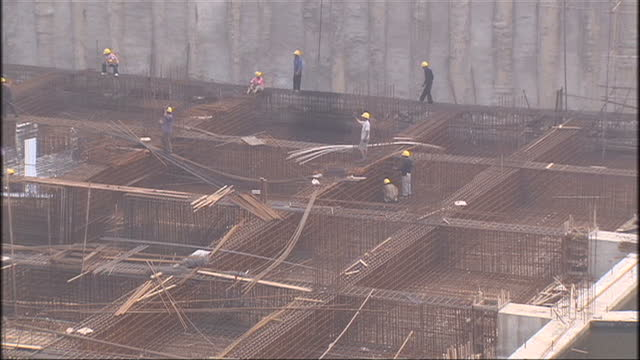 exterior shots of construction workers walking on a half built structure and construction materials being lifted by machinery whilst workers are... - 2008年北京夏季オリンピック点の映像素材/bロール