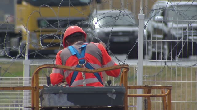 Exterior shots of construction workers working on part of a security fence around the port of Calais part of security measures to prevent illegal...
