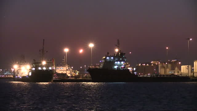 Exterior shots of container ships and an oil refinery with flaming chimneys in the port of Ras Laffan at night time on December 22 2014 in Ras Laffan...