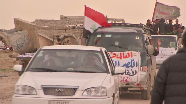 exterior shots of convoy of vehicles draped in iraqi flag driving through hamam alalil refugee camp and shots of people walking around on march 28... - iraqi flag stock videos and b-roll footage