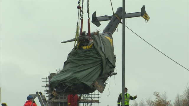 exterior shots of crashed police helicopter being lifted by crane from damaged pub covered in tarpaulin investigation into friday's police helicopter... - ヘリコプター事故点の映像素材/bロール