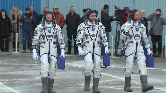 exterior shots of crew of soyuz mission tma19m tim peake commander yuri malenchenko timothy kopra walk out of building and stand in a line before... - 乗員点の映像素材/bロール