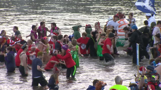 exterior shots of crowd in water at firth of forth river taking part in loony dook swimming event new years day tradition and all posing for photos... - swimming costume stock videos and b-roll footage