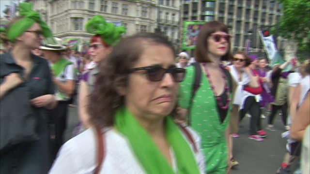 Exterior shots of crowds and women marching to mark the 100 year anniversary of the right to vote for women wearing suffragette colours of green...