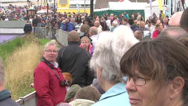 exterior shots of crowds at the clacton airshow as an announcer reads out a memorial to the shoreham air crash victims and the crowd observing... - ショーハム・バイ・シー点の映像素材/bロール