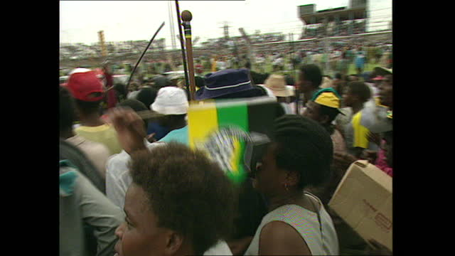 exterior shots of crowds celebrating and holding posters of nelson mandela at the anc 82nd anniversary rally at orlando stadium on the 8th january... - ソウェト点の映像素材/bロール