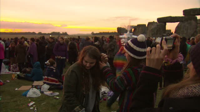 vídeos y material grabado en eventos de stock de exterior shots of crowds gathered at stonehenge during sunrise to celebrate the summer solstice, including a person walking through the crowd wearing... - solsticio de verano