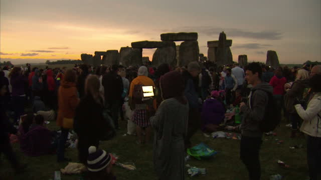 vídeos y material grabado en eventos de stock de exterior shots of crowds gathered at stonehenge to watch the sun rise during summer solstice celebrations, many looking at their mobile phones or... - solsticio de verano