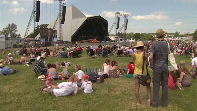 exterior shots of crowds gathering in a field near the pyramid stage on the opening day of glastonbury festival many people sunbathing due to the hot... - fußballweltmeisterschaft 2010 stock-videos und b-roll-filmmaterial