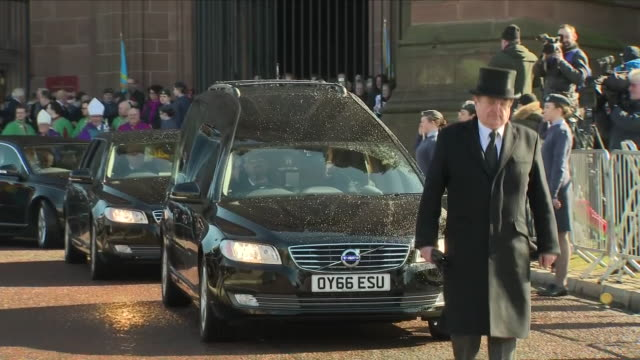 vídeos de stock, filmes e b-roll de exterior shots of crowds lining the street as the funeral cortege for sir ken dodd departs from liverpool cathedral after a public funeral service... - pano de pó