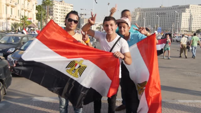 vidéos et rushes de exterior shots of crowds of egyptian people on the streets of cairo in cars and on foot, waving egyptian flags and cheering after the opening of a... - port saïd