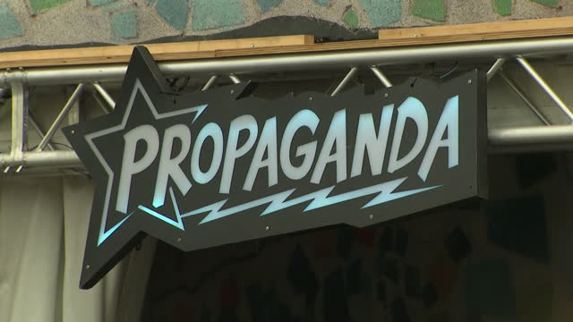 Exterior shots of crowds of festival goers drinking outside the 'Chameleon Bar' at Glastonbury Festival with signs reading 'Propaganda' during a...