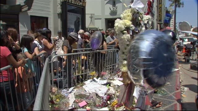 vídeos de stock e filmes b-roll de exterior shots of crowds of michael jackson fans outside mann's chinese theatre with numerous messages of sympathy, flowers and balloons after the... - morte