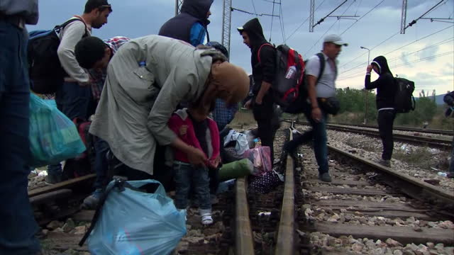 exterior shots of crowds of migrants walking along train tracks on the border between greece and serbia on september 11 2015 in athens greece - greece stock videos & royalty-free footage