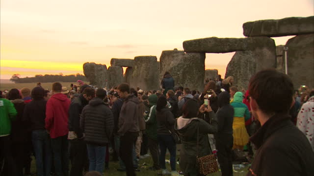 vídeos y material grabado en eventos de stock de exterior shots of crowds of people gathered at stonehenge watching the sun rise during summer solstice celebrations.>> on june 21, 2015 in amesbury,... - solsticio de verano