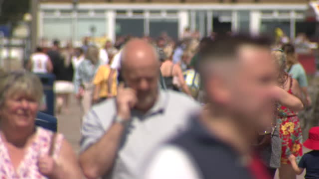 exterior shots of crowds of people visiting porthcawl beach walking on the promenade and eating lunch on a sunny bank holiday monday on the 31st may... - eating stock videos & royalty-free footage