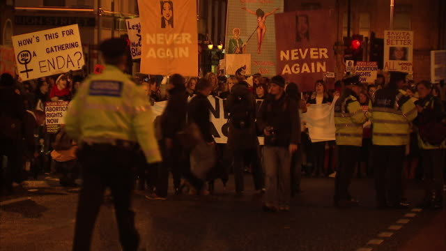 exterior shots of crowds of prochoice protesters carrying 'never again' placards in street demonstration against irish abortion laws after the death... - moving activity stock videos & royalty-free footage
