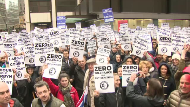 exterior shots of crowds of protesters gathered holding union jack flags and posters 'zero tolerance for antisemitism' and 'labour: hold corbyn to... - 反ユダヤ主義点の映像素材/bロール