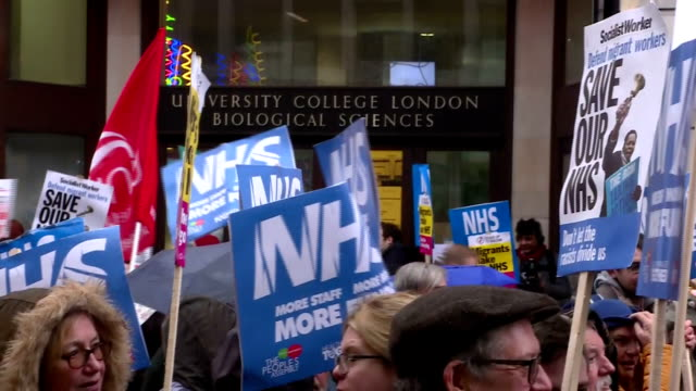 exterior shots of crowds of protesters marching through central london carrying banners and placards calling for better funding for the nhs including... - nhs stock videos & royalty-free footage