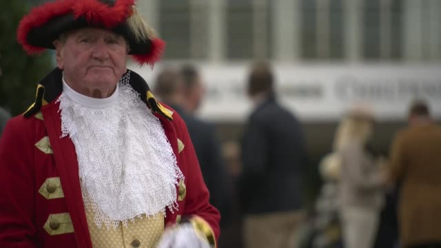 vídeos de stock, filmes e b-roll de exterior shots of crowds of racegoers walking into the cheltenham festival on gold cup day as a town crier rings a bell and shouts on 15 march 2019... - cheltenham