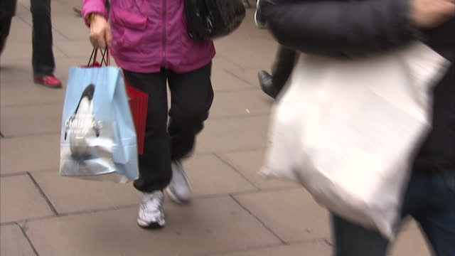 exterior shots of crowds of shoppers on oxford street near a branch of bhs with large signs advertising black friday sales.>> on november 28, 2014 in... - black friday stock videos & royalty-free footage