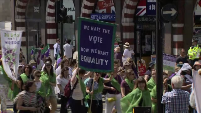 Exterior shots of crowds of women and girls marching holding banners and placards and wearing the suffragettes colours of green white and violet as...