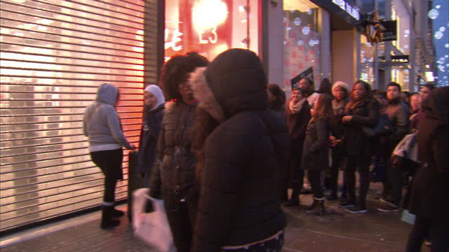 exterior shots of crowds waiting outside new look on oxford street and hurrying inside as the shutters raise at the start of the boxing day sales... - markenname stock-videos und b-roll-filmmaterial