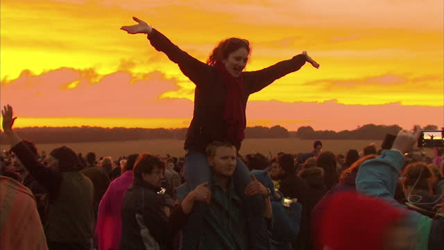 vídeos y material grabado en eventos de stock de exterior shots of crowds watching the sun rise and posing for photographs during summer solstice celebrations at stonehenge.>> on june 21, 2015 in... - solsticio de verano