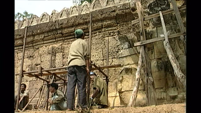 exterior shots of crumbling buddhist temples of preah khan at angkor wat in a state of disrepair as craftsmen and women draw up plans and carry out... - angkor stock videos and b-roll footage