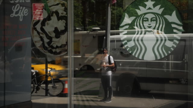 Exterior shots of customers sat inside Starbucks with people walking past outside including shots of their reflections being shown on the Starbucks...