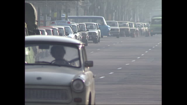 exterior shots of daily life around east berlin, including trabants and russian made cars driving on roads, a street cleaner and people walking down... - east berlin stock videos & royalty-free footage