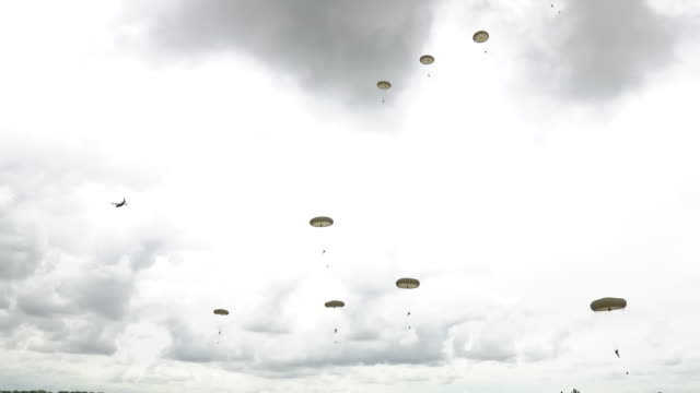 exterior shots of dakota transport planes flying overhead as parachutists drop from them as part of 75th anniversary commemorations of dday as crowds... - parachuting stock videos & royalty-free footage