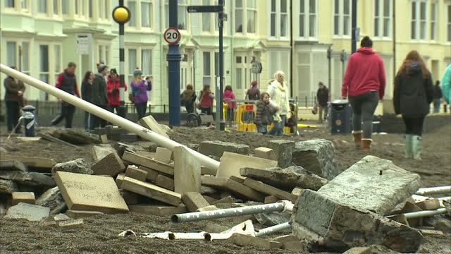 vídeos de stock, filmes e b-roll de exterior shots of damage to the aberystwyth seafront with broken railings and paving slabs scattered across the beach and local people surveying the... - aberystwyth