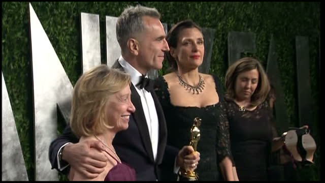 Exterior shots of Daniel Day Lewis posing for photos with Oscar award and women either side of him on Vanity Fair red carpet Vanity Fair Party on...