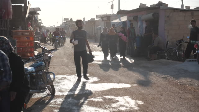 vídeos de stock, filmes e b-roll de exterior shots of day to day life around an idlib province unhcr refugee camp including an injured child people walking and men on motorcycles on 17... - arab spring