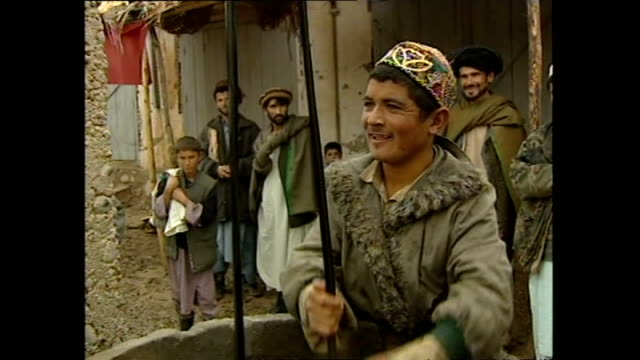 vidéos et rushes de exterior shots of day to day life around the afghan town of khuj a bahuddin including a shopkeeper listening to a radio and a man drawing water from... - guerre d'afghanistan : de 2001 à nos jours