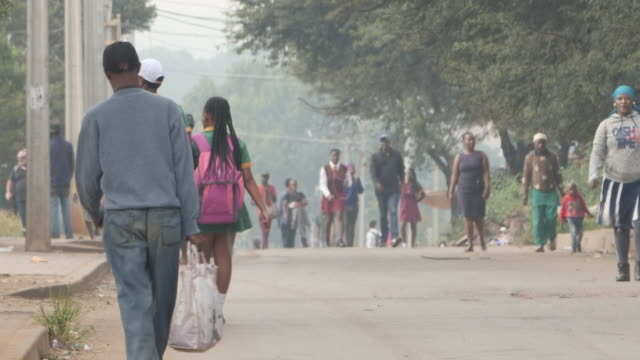 exterior shots of day-to day life around soweto with people walking in streets and school pupils returning home on 11 march 2020 in soweto, south... - ソウェト点の映像素材/bロール