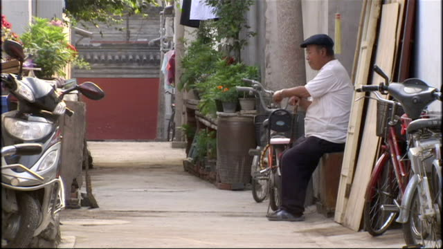 exterior shots of day-to-day life in a beijing hutong, or alley, with an old man sat by a wall and people buying goods at a convenience store on july... - hutong alley stock videos & royalty-free footage