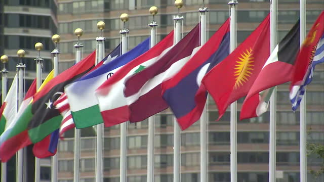 exterior shots of delegates queueing outside the united nations headquarters in new york and flags of member states flying nearby>> on september 27... - 国際連合点の映像素材/bロール