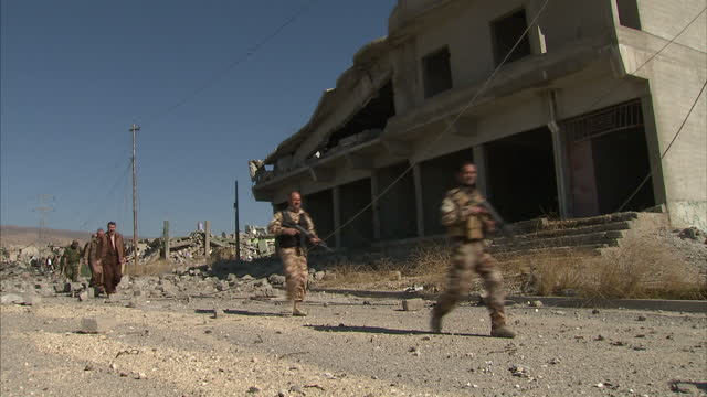 stockvideo's en b-roll-footage met exterior shots of destroyed buildings from explosions and kurdish peshmerga troops yazidi volunteer fighters walk through streets and buildings of... - puin
