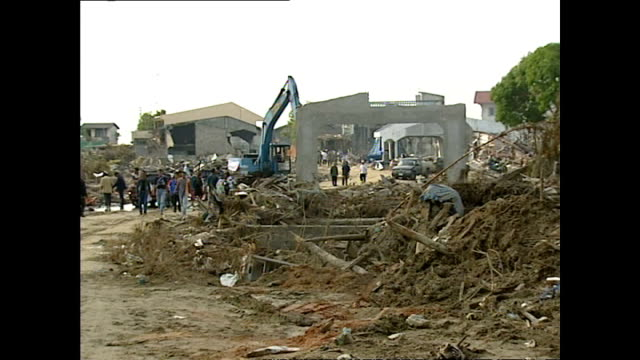 exterior shots of destruction and debris in nam kem village with heavy machinery being used to clear away rubble and debris from buildings destroyed... - 2004 stock-videos und b-roll-filmmaterial