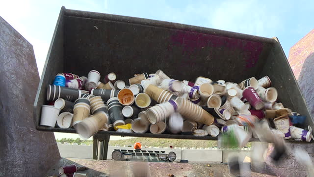 vídeos de stock, filmes e b-roll de exterior shots of digger moving pile of used disposable cups at a recyling plant researchers say charging for disposable coffee cups could cut the... - xícara de café