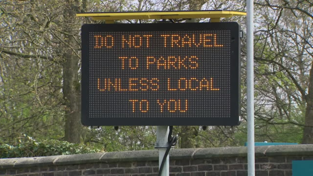 exterior shots of digital sign outside of heaton park displaying social distancing rules and shots of a closed off playground and very few visitors... - group of people stock videos & royalty-free footage