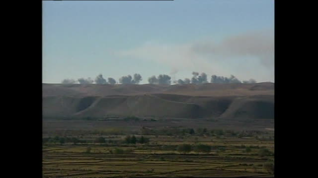 vídeos de stock, filmes e b-roll de exterior shots of distant explosions onto taliban positions in northern afghanistan with plumes of smoke and vapour trails from a b52 bomber on... - afeganistão
