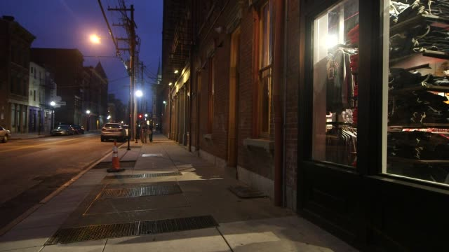 Exterior shots of downtown in Cincinatti Ohio at night in fall on 1292014 Wide shot of storefronts and the apartments above Wide shot of a sidewalk...