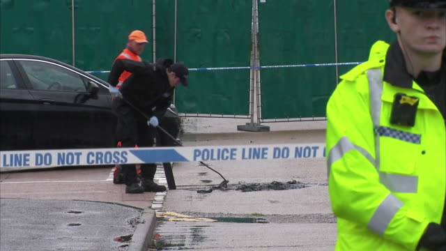 vidéos et rushes de exterior shots of drains being searched at the crime scene where a lorry was found to have 39 bodies in its container at waterglade industrial park... - détective