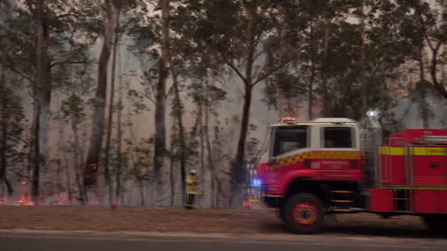 exterior shots of driving by fire with fire trucks and firefighters on the side on the road on 5 january 2020 in australia. - australia stock videos & royalty-free footage