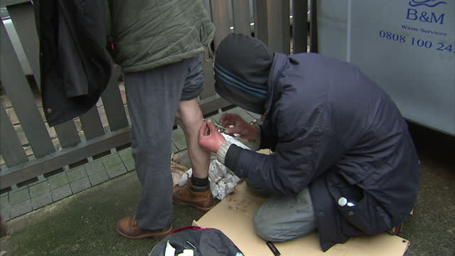 Exterior shots of drug addicts measuring up heroin fix dose cleaning part of leg with disinfectant wipe and injecting into leg on December 02 2014 in...